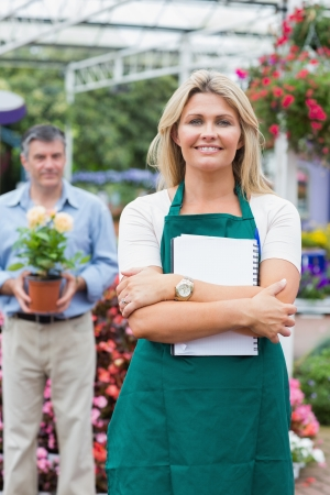 Customer holding a flower with woman holding a notepad in garden center Stock Photo - 16068143