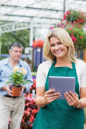 Cheerful florist holding a tablet pc in garden center with customer standing behing holding flower pot Stock Photo - 16068107