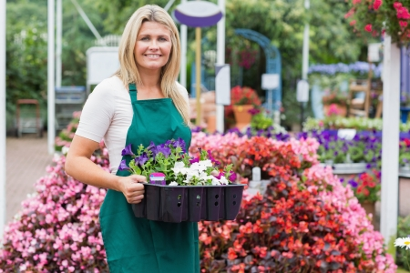 Woman holding a flower box while smiling photo