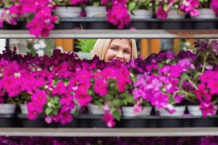 Woman smiling through shelves in garden center