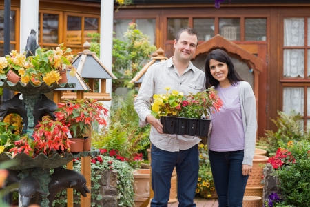 Smiling couple carrying tray of plants in garden center photo