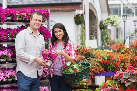 Happy couple shopping for flowers holding a basket in garden center