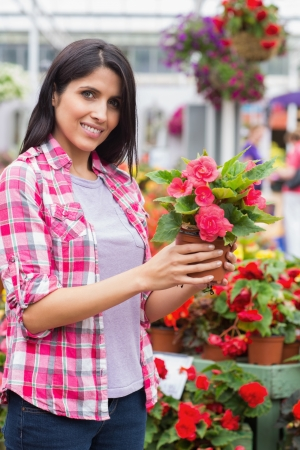 tuincentrum: Smiling woman in garden center holding a flower
