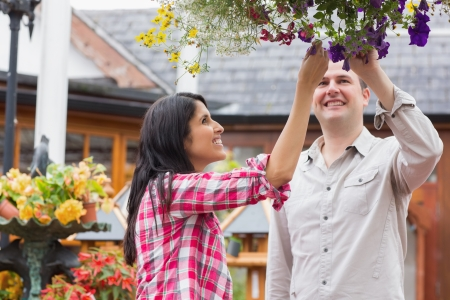 Couple touching flowers in hanging basket in garden center photo