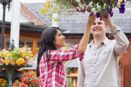 hanging basket: Couple touching flowers in hanging basket in garden center