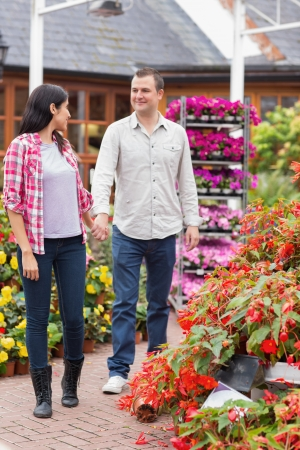 Couple walking in garden centre while smiling and holding hands photo