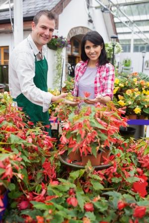 garden center: Smiling customer touching plant with employee in garden center