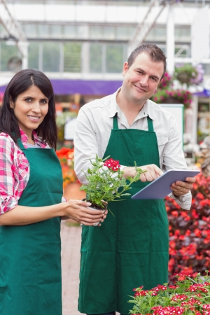 taking inventory: Happy workers using tablet pc and holding flower pot in garden center Stock Photo