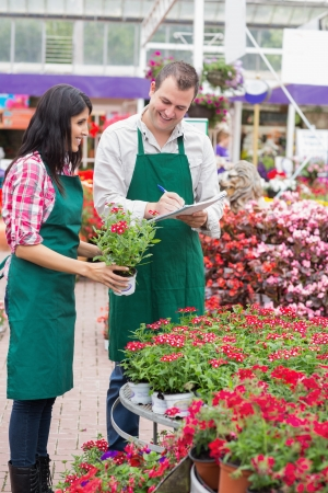 taking inventory: Two garden center employees making notes on flower pots