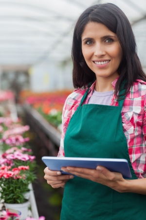Woman doing inventory with laptop in working in greenhouse photo