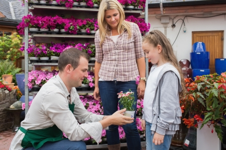 garden center: Garden center worker giving a flower to child while her mother standing next to her