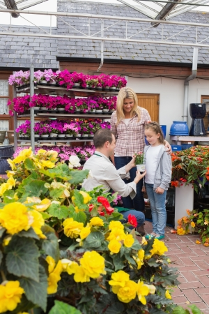 Woman and child taking a flower pot from employee in garden center photo