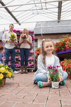 Happy family holding flower pots with little girl sitting on ground in garden centre photo