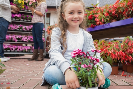 Little girl holding flowers while smiling sitting on path of garden center photo