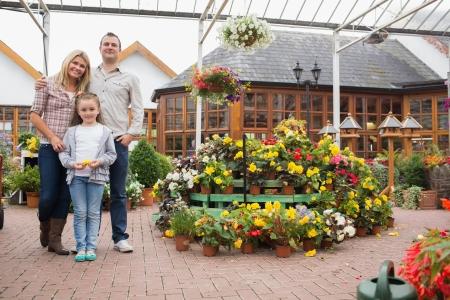 Happy family standing in the garden center Imagens