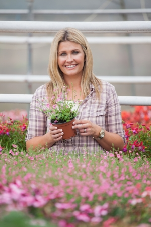 Woman holding a flower while standing in greenhouse of garden center photo