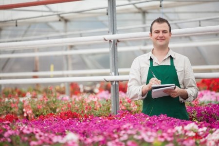 Smiling man taking notes in the greenhouse in garden center Stock Photo