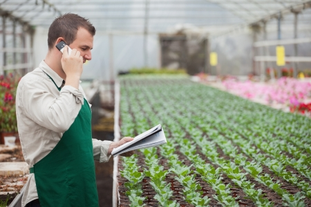 Gardener calling and taking notes for stocktaking in greenhouse nursery photo