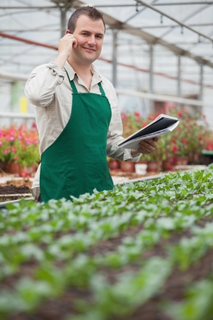 Smiling man on the phone and taking notes in greenhouse in garden center photo