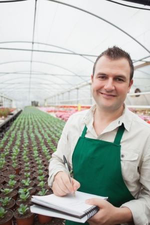 taking inventory: Smiling man taking notes in greenhouse nursery Stock Photo