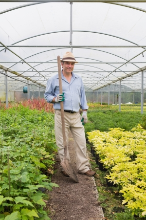Gardener holding a spade while smiling and standing in greenhouse photo
