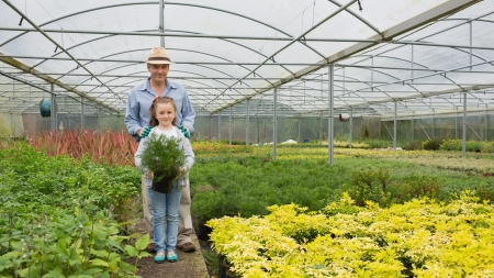 grandddaughter: Gardener and grandddaughter in the greenhouse holding large potted plant