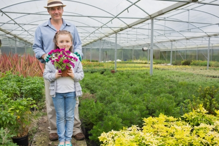 Gardener standing with granddaughte holding a flower pot photo