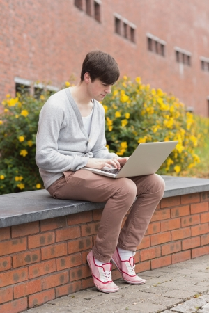 Student using laptop sitting on wall outside in college photo