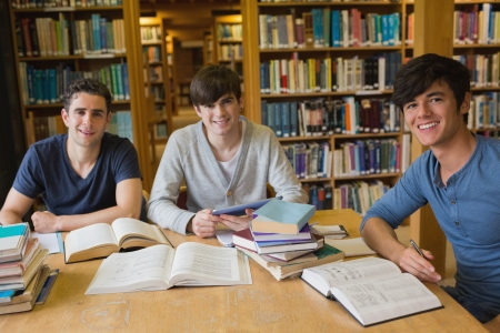 Students looking up from studying and smiling in the library photo