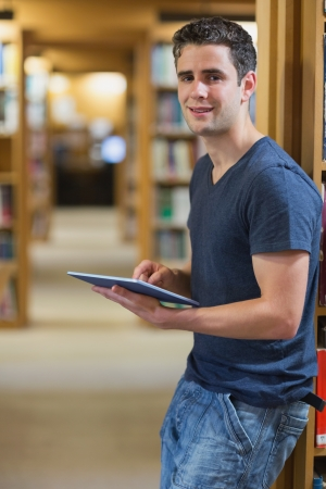 Man leaning at a wall at the library holding a tablet PC smiling  photo