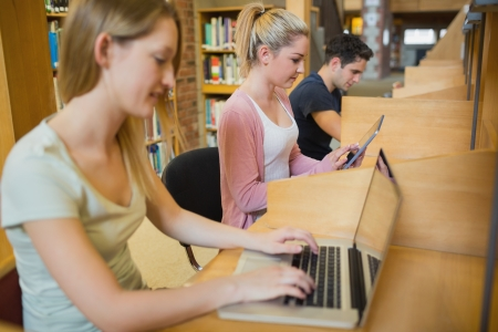 Students studying in a row at study desks in college library Stock Photo - 16076956