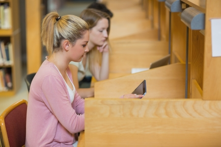Woman using tablet pc to study at desks in college library photo