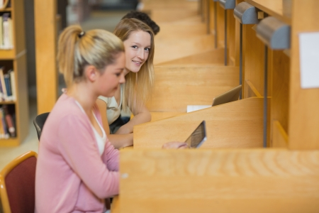 Woman looking up from studying at study desks in college library photo