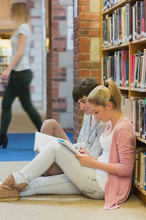 Boy and girl sitting on floor of college library studying against a bookshelf photo