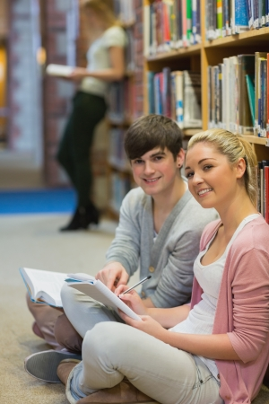 Man and woman sitting in front of a bookshelf at the library while smiling  photo