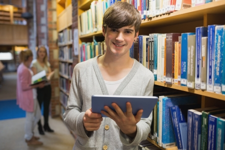 Man standing at a bookshelf holding a tablet pc in college library photo