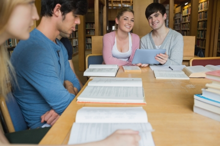 Students sitting at library table smiling while holding a tablet pc in college photo