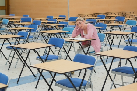 student desk: Student sitting and talking at desk in empty exam hall Stock Photo
