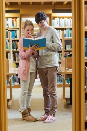 Couple standing at the library between the bookshelves looking at a book photo