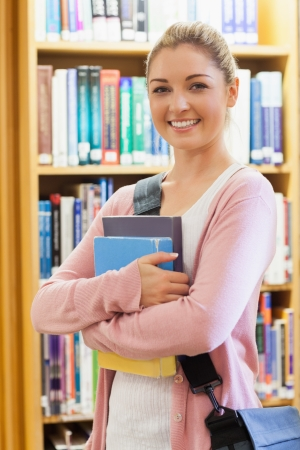 Student standing at the library holding books photo