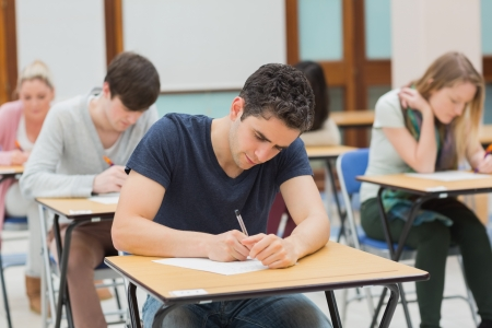 Students sitting in an exam hall doing an exam in university photo