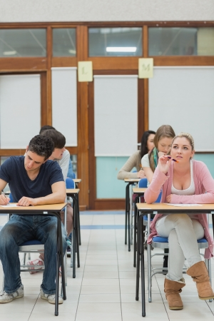 Students in an exam hall while one is thinking in college photo