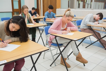 People sitting at the classroom and writing writing photo