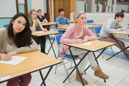 Students sitting at the classroom while writing Stock Photo - 16065901