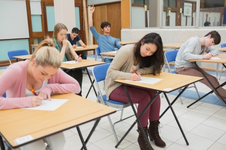 examination room: Students sitting at the classroom while student is raising hand to ask question