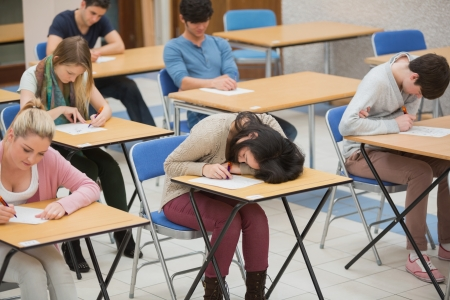 Girl sleeping on desk during exam in exam hall photo