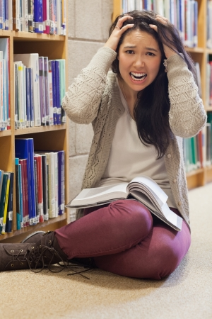 Stressed student sitting on library floor with book on her lap photo