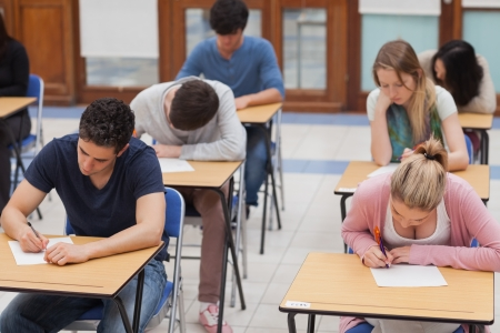 Students sitting a test in an exam hall in college Stock Photo