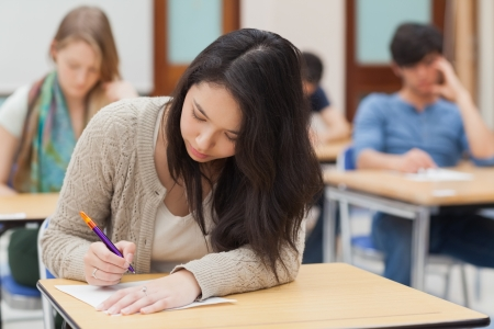 Woman doing an exam in exam hall in college photo