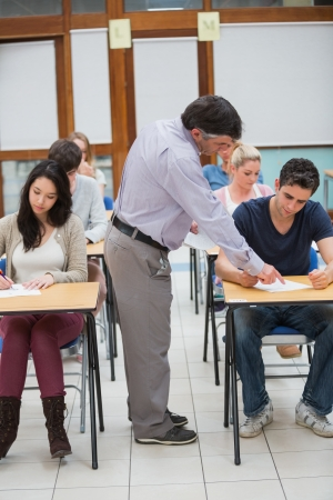educational institution: Lecturer helping student in classrom